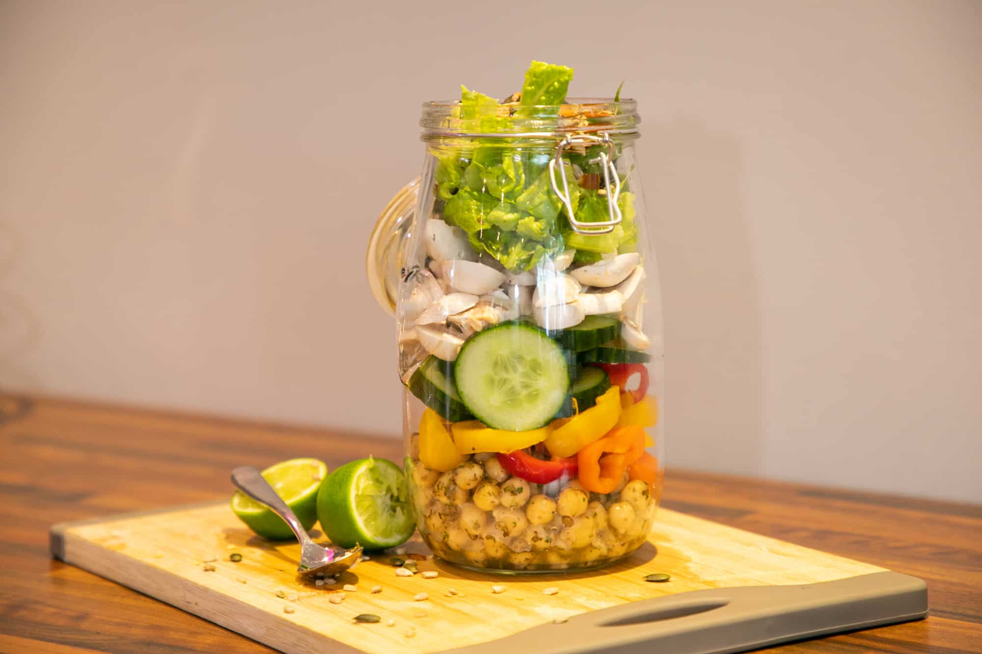 fresh salad arranged in a glass jar with lid