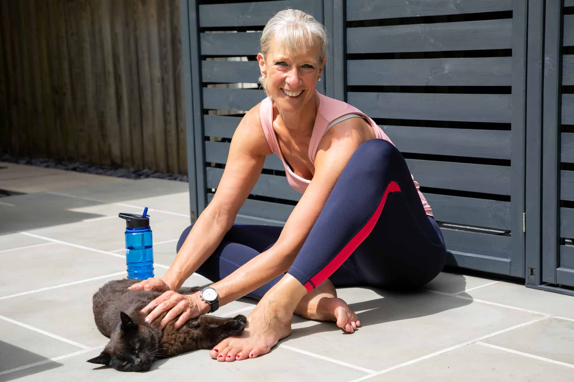 Personal Trainer Carola Becker sitting on the floor with black cat